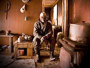 An elderly african-american man sits inside of his garage.