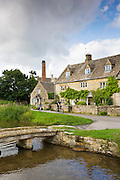 Cyclists in popular tourist attraction village Lower Slaughter in The Cotswolds, Gloucestershire, UK