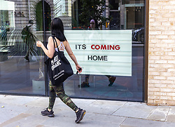 Licensed to London News Pictures. 08/07/2021. London, UK. Members of the public walk past an 'It's coming home' sign in Chelsea, southwest London as fans nursed hangovers this morning after celebrating into the night after England's dramatic win against Denmark in the Euro 2020 Semi-finals at iconic Wembley Stadium. The England team will be back at Wembley this Sunday (11 July 2021) for the first time since 1968 as they take on Italy for a chance to win the European cup for the first time ever. Photo credit: Alex Lentati/LNP