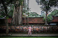 A woman exercises on a sidewalk beside the Temple of Literature in Hanoi, Vietnam, Southeast Asia
