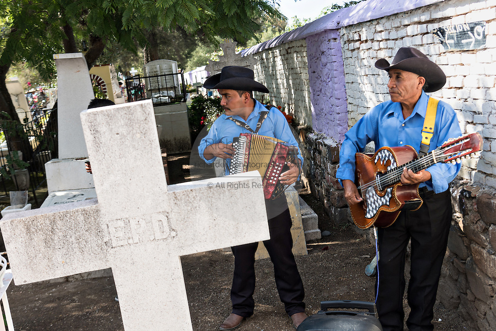 A mariachi band plays at a gravesite in the Nuestra Señora de Guadalupe cemetery during the Day of the Dead festival November 1, 2016 in San Miguel de Allende, Guanajuato, Mexico. The week-long celebration is a time when Mexicans welcome the dead back to earth for a visit and celebrate life.