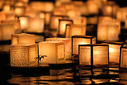 Memory lanterns lit by candle float in the waters off Ala Moana Beach Park.