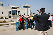 Visitors pose for a photograph outside the Charriots Exhibition Hall, Qin Museum, Xian, China