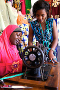 """Rahab Mbuba teaching a student some of her sewing techniques.<br /> <br /> Rahab, also known as 'Mama B"""", set up and now runs a tailoring business, designing and making clothes.<br /> <br /> She attended MKUBWA enterprise training run by the Tanzania Gatsby Trust in partnership with The Cherie Blair Foundation for Women."""
