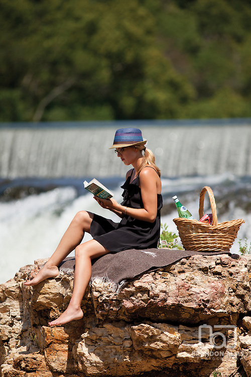 A woman reads a book on a rock in Grand Falls located in Joplin, Missouri.
