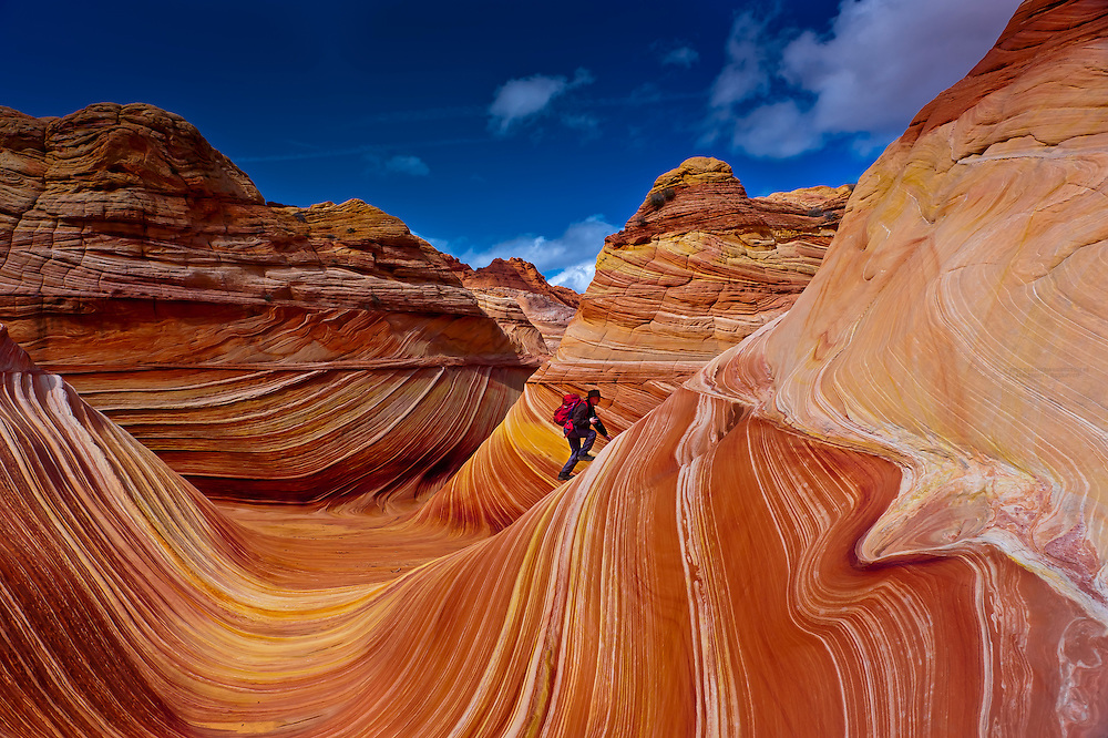 """Hiker exploring """"The Wave"""", a 190 million year old Jurassic-age Navajo sandstone rock formation, Coyote Buttes, Paria Canyon-Vermillion Cliffs Wilderness Area, Utah-Arizona border, USA"""