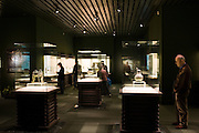 Visitors look at bronze objects on display in glass cases at the Shanghai Museum, China