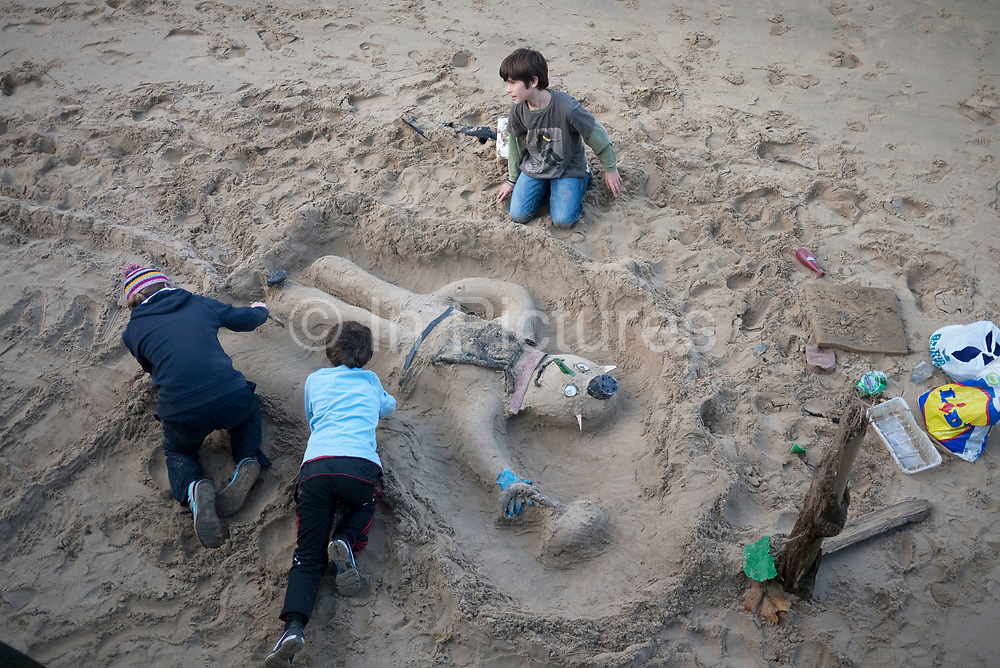Kids play in the sand on the Southbank beach, London.As the Thames reaches low tide, this small sandy beach is revealed where children can have fun in the sand. Here, three young boys make the character of a man.