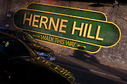 The large sign under the railway bridge announcing Herne Hill, Lambeth SE24 south London. The mural is one of many in south London by the artist Lionel Stanhope.