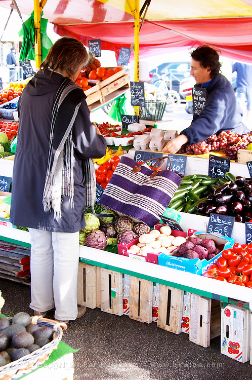 Street market merchant's stall with vegetables, a woman shopping with a basket Sanary Var Cote d'Azur France