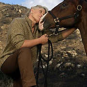 """Joan Embery rescued 30 wild animals and 30 horses from her Lakeside Ranch as the fire roared up to the property line. Embery is seen with """"Mugger"""", a 7-yr-old mountain lion, """"Claudia"""" an Andean Condor, and Belles Peppy Boy, Joan's favorite horse. Photographed at the site where Joan and Duane (seen with her in the photos of horses), along with employees, beat the flames from the Cedar Fire that reached their ranch.  .© Todd Bigelow/Aurora."""