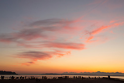 United States, Washington, Seattle, people on dock by Elliott Bay  at sunset with Olympic Mountains beyond