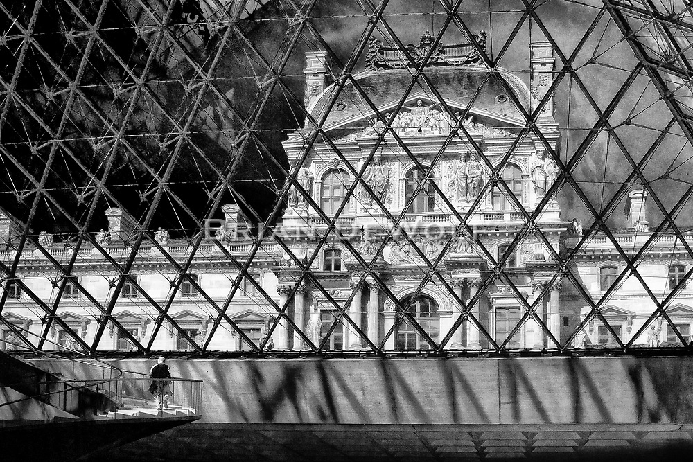 View of the Musee de Louvre from inside the Louvre Pyramid.  This viewing pyramid acts as the main entrance to the museum. The man on the stairway at the bottom left lends scale to the enormous structure.  Aspect Ratio 1w x 0.667h.