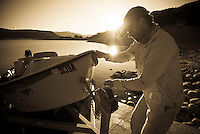A fisherman loads his boat onto a trailer at sunset in northwest Wyoming.