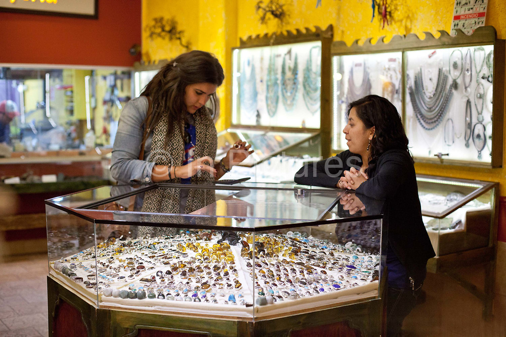 Young woman trying on Amber jewellery in a small boutique shop with the shop assistant showing her the items for sale. San Cristobal de las Casas, Chiapas, Mexico.