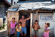 "Roma settlement Ostrovany. Marian with his family in front of their house located at the Roma settlement  Ostrovany in East Slovakia. Marian: ""We are devided (by the fence) - into white and the gypsies. When there was no fence some of the people stole just some fruits and vegetables. The ""Berlin Wall"" does not matter for us anymore, standing there already a few years. They were building it well."" In 2010, the town of Ostrovany received international media attention when the town council built a wall dividing private gardens and the neighboring Roma settlement. Several media outlets compared the look of Ostrovany's 150 m long wall with the Berlin Wall. Mayor Mr. Rehak sees the building as a ""fence"" and not a wall."