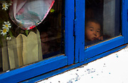 A young boy peers out of a nursery at Yonsan <br /> <br /> <br /> ©Jeremy Horner<br /> 15 Mar 2004