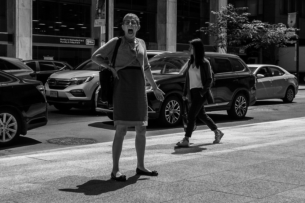 The true excitement of photographing on the street is when you find something exciting and unexpected. This lady paused and then gave a big yawn; fortunately I was in a good angle and was able to quickly react. I especially like this image because, not only of the yawn but also because of the traffic of the street. The cars add to the feeling of busyness. Taken on King Street near Yonge.