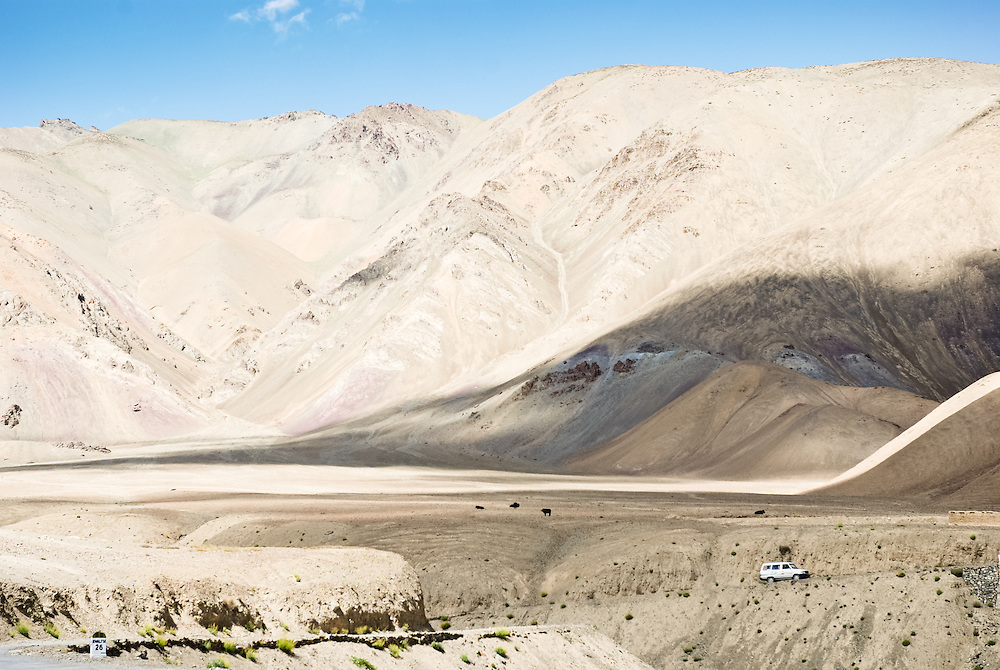 A jeep passes through a stunning high altitude landscape in Ladakh