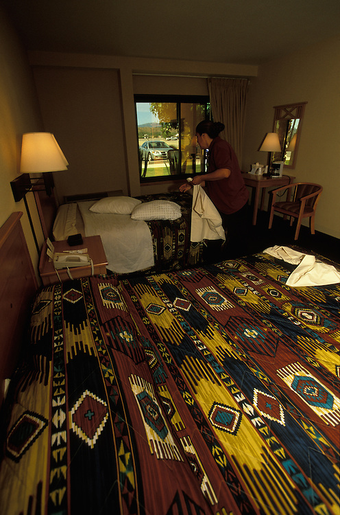 A maid makes up a room in the Best Western Motel attached to the Apache Gold Casino on the San Carlos Apache Indian Reservation in Arizona, USA. June 2004.