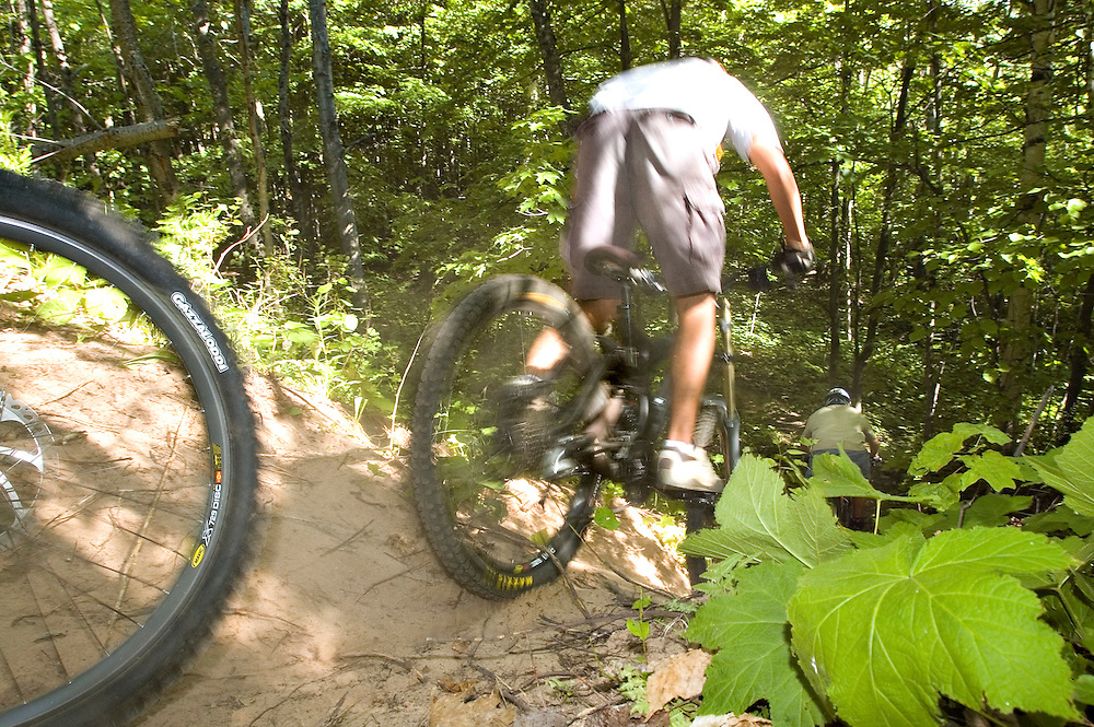Mountain bikers drop down a steep section of trail while freeriding near Marquette Michigan.