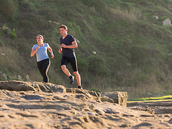 Man and woman jogging on single trail