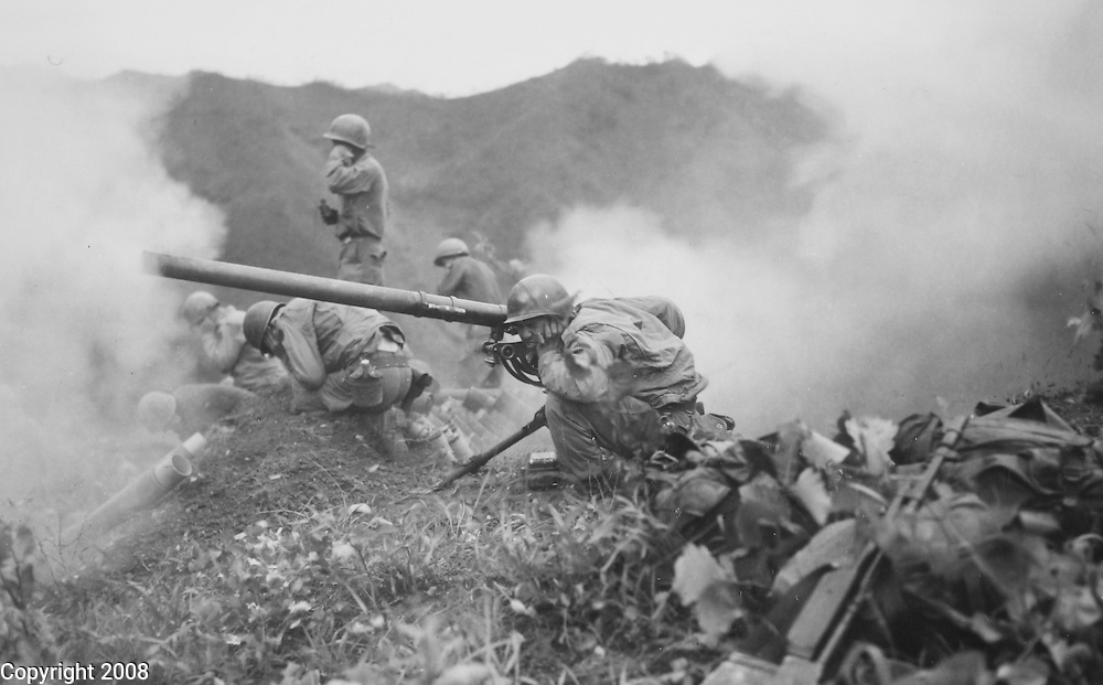 PFC Roman Prauty (crouching foreground) gunner, 7th U.S. infantry division with the assistance of his gun crew fires a T5MM recoiless rifle during the Korean War in support of infantry units directrly across the valley around June 9, 1951.