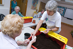 Women taking part in a Thrive gardening workshop for visually impaired people visiting the NRSB,  The use of yellow and red boxes help visually impaired people such as those with macular degeneration,