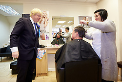 © Licensed to London News Pictures.  02/05/2015. ABINGDON, UK. Boris Johnson talks to customers and staff in a barber shop voters while campaigning in Abingdon with Nicola Blackwood (not seen) who is standing for re-election as MP for the Oxford West and Abingdon constituency. Photo credit: Cliff Hide/LNP