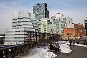 Two people sit and talk on a bench surrounded by snow on the High Line walkway over 10th Avenue; Chelsea; New York City; New York, United States of America.  The iconic InterAtiveCorp building is in the background.