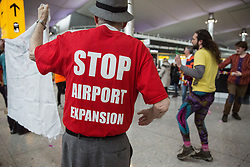 Campaigners against airport expansion from Rising Up, a predecessor of Extinction Rebellion, stage a flashmob and die-in at Heathrow Airport's Terminal 2 on 18th February 2017 at Heathrow, United Kingdom. The activists were protesting against proposals to build a third runway at Heathrow Airport in order to permit an additional 250,000 flights a year.