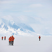 A group of people walk across the fast ice in front of a snow-covered mountain in Crystal Sound in Antarctica.