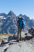 Backpacker at Boulder Pass . Thunderbird Mountain is in the distance. Glacier National Park Montana