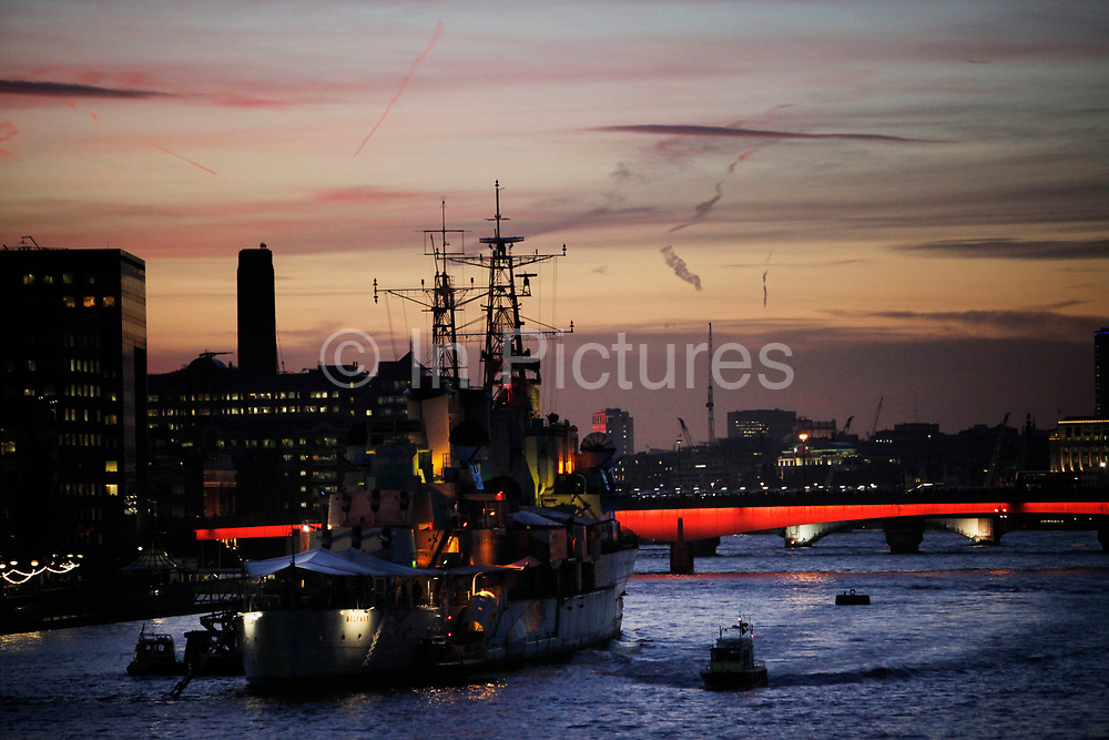 HMS Belfast on the River Thames as night falls and the sunset eases into the evening. HMS Belfast is one of the icons of the River Thames. Moored just along from London Bridge, HMS Belfast is a museum ship,  permanently moored in London on the River Thames. She was originally a Royal Navy light cruiser and served during the Second World War and Korean War.