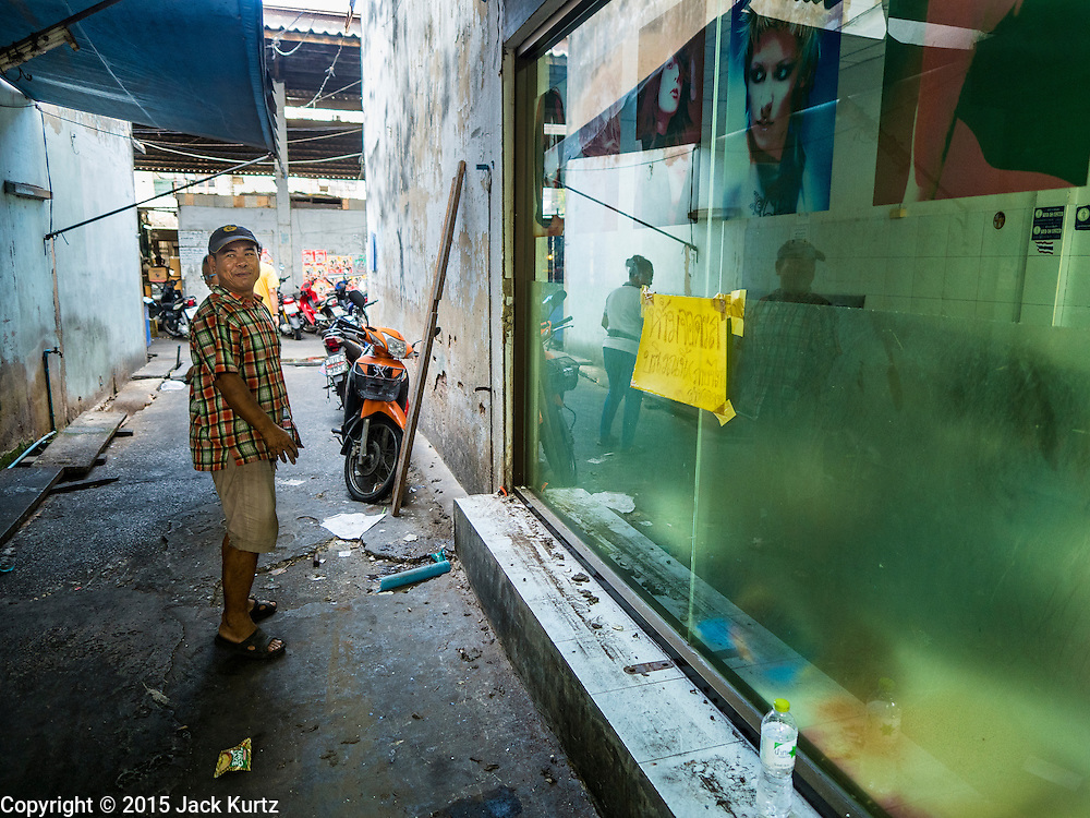 31 DECEMBER 2015 - BANGKOK, THAILAND: A demolition worker walks past a beauty shop he is tearing down in Bang Chak Market after the shop was closed. The market is supposed to close permanently on Dec 31, 2015. The Bang Chak Market serves the community around Sois 91-97 on Sukhumvit Road in the Bangkok suburbs. About half of the market has been torn down. Bangkok city authorities put up notices in late November that the market would be closed by January 1, 2016 and redevelopment would start shortly after that. Market vendors said condominiums are being built on the land.          PHOTO BY JACK KURTZ