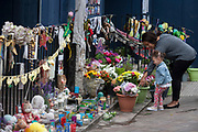 A young child looks at flowers left near where the Grenfell fire occured, on the first anniversary of the tower block disaster, on 14th June 2018, in London, England. 72 people died when the tower block in the borough of Kensington & Chelsea were killed in what has been called the largest fire since WW2. The 24-storey Grenfell Tower block of public housing flats in North Kensington, West London, United Kingdom. It caused 72 deaths, out of the 293 people in the building, including 2 who escaped and died in hospital. Over 70 were injured and left traumatised. A 72-second national silence was held at midday, also observed across the country, including at government buildings, Parliament.