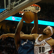 PHOTO BY DAVID RICHARD.Drew Gooden of Cleveland puts a hard foul on Washington's Caron Butler in the first game of the playoffs against the Wizards.