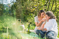 Woman feeding man with cheese on meadow, Germany