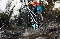 Low section of mountain biker crossing stream in a forest, Bavaria, Germany
