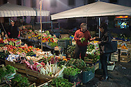 A woman pays for vegetables at an outside vegetable stand in Naples, Italy