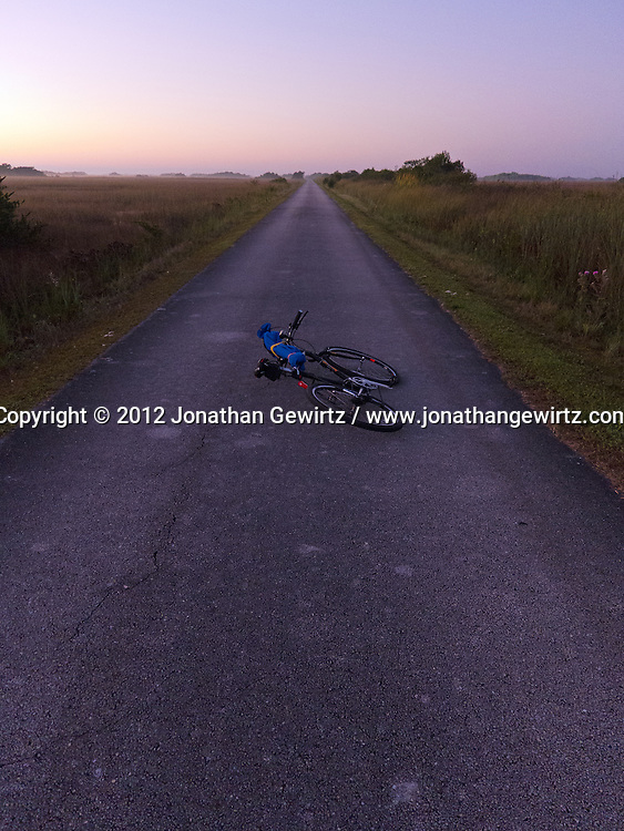 A bicycle carrying a photo tripod lies on the paved bicycle and pedestrian path in the Shark Valley section of Everglades National Park, Florida. WATERMARKS WILL NOT APPEAR ON PRINTS OR LICENSED IMAGES.