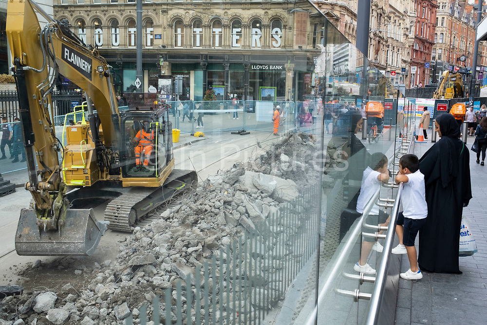 Onlookers watch as a workman operating a digger lifts large quantities of rubble into a truck at the construction site for work on the update to the Midland Metro tram public transport system in the city centre along Corporation Street on 3rd August 2021 in Birmingham, United Kingdom. The original tracks are being pulled up and relaid, while a new line is also under construction and due to open later in the year. The Midland Metro is a light-rail tram line in the county of West Midlands, England, operating between the cities of Birmingham and Wolverhampton via the towns of West Bromwich and Wednesbury. The line operates on streets in urban areas, and reopened conventional rail tracks that link the towns and cities. The owners are Transport for West Midlands with operation by National Express Midland Metro, a subsidiary of National Express. TfWM itself will operate the service from October 2018.