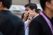 """15 NOVEMBER 2013 - BANGKOK, THAILAND: Former Thai Prime Minister ABHISIT VEJJAJIVA and leader of the Thai Democrat party, covers his mouth while he makes a mobile phone call at an anti-government protest in Bangkok. Tens of thousands of Thais packed the area around Democracy Monument in the old part of Bangkok Friday night to protest against efforts by the ruling Pheu Thai party to pass an amnesty bill that could lead to the return of former Prime Minister Thaksin Shinawatra. Protest leader and former Deputy Prime Minister Suthep Thaugsuban announced an all-out drive to eradicate the """"Thaksin regime."""" The protest Friday was the biggest since the amnesty bill issue percolated back into the public consciousness. The anti-government protesters have vowed to continue their protests even though the Thai Senate voted down the bill, thus killing it for at least six months.     PHOTO BY JACK KURTZ"""