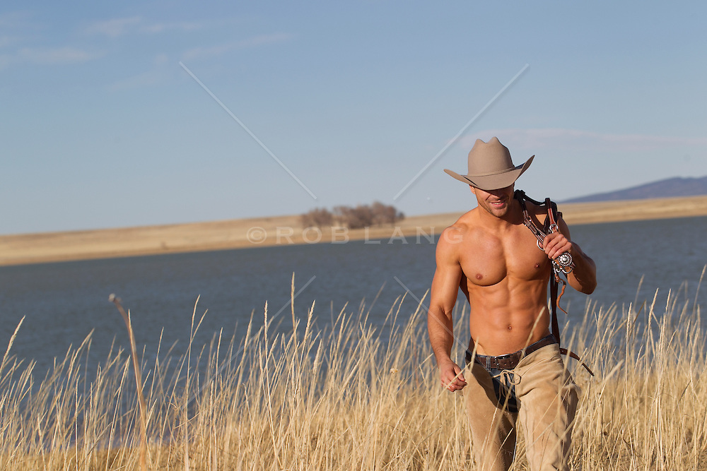 shirtless cowboy in chaps walking through tall grass by a lake in New Mexico