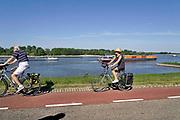 Nederland, Ooijpolder, 21-5-2020 Recreatie, fietsers, op de waaldijk op deze mooie hemelvaartsdag . In de rivier vaart een binnenvaartschip beladen met containers voorbij .Foto: Flip Franssen