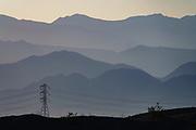 Mountains of Santa Rosa Wilderness rise above powerlines near Mecca, California, USA.
