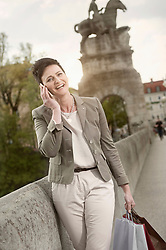 Mature woman talking on mobile phone in city with shopping bags, Bavaria, Germany