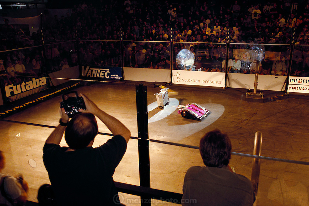 Ringed by six-foot sheets of bulletproof glass and a sellout crowd, radio-controlled gladiators battle to the mechanical death. At Robot Wars, a two-day-long competition in San Francisco, the crowd roars to the near-constant shriek of metal, the crash of flying parts, and the thunderous beat of techno music. After a series of one-on-one matches, losers and winners alike duke it out in a final death-match called a Melee. California, USA