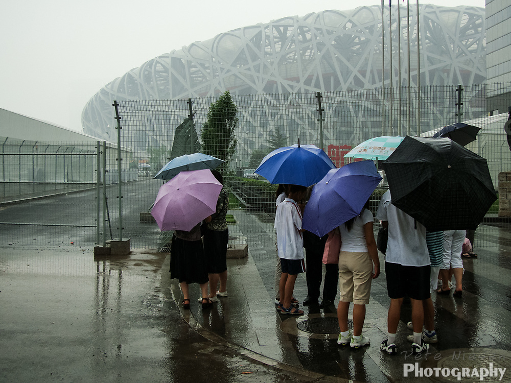 Tourists standing in the rain outside Beijing's Bird Nest National Stadium during construction