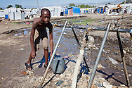 Boy getting water provided in a tent city in Port-au-Prince that is untreated. The lack of clean water makes Haiti ripe for the spread of cholera.  Since the earthquake on January 12, 2010, thousands still live in tent cities that lack sanitation.